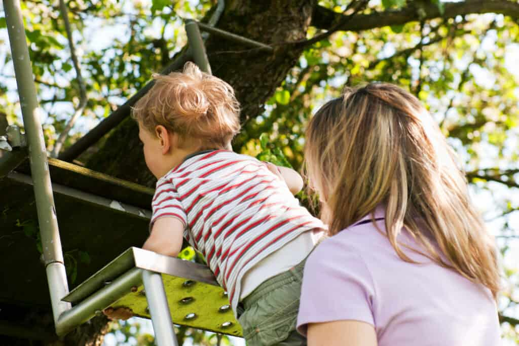 mom helping child climb stairs outside thanks to knowing authoritarian vs authoritative parenting
