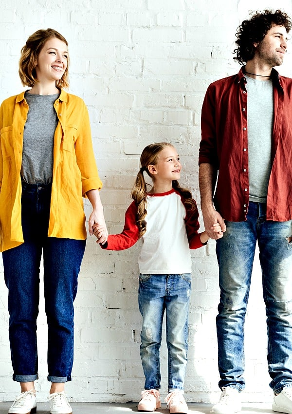 attractive mom and dad with cute daughter displaying good parenting skills while holding her hand