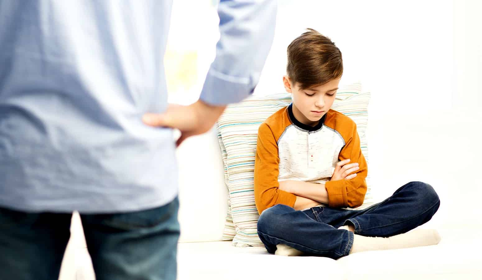 Little boy in orange shirt pouting with dad because of consequences for bad behavior