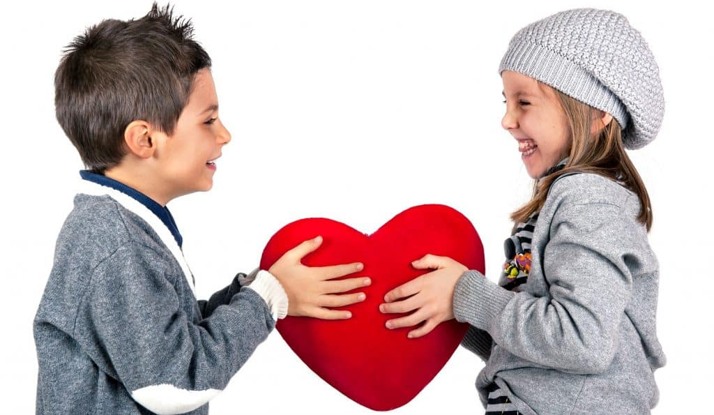 two kids playing with a red heart while celebrate Valentine's Day with your kids