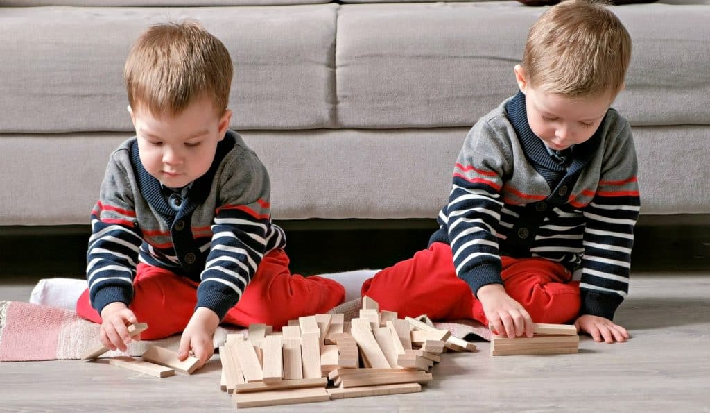 two toddler boys on the floor playing the best board games for toddlers jenga