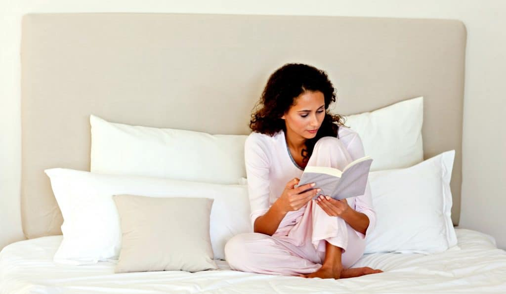 mom in bed reading the best christian parenting books