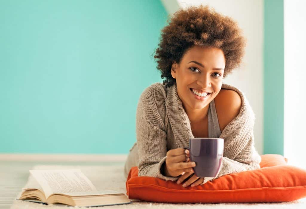 young pretty woman reduce family stress with self care while drinking tea and reading a book