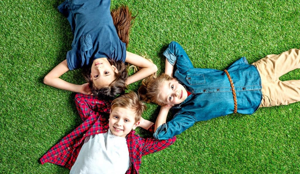 three children with different child termperament types lying on the green grass with hands under heads