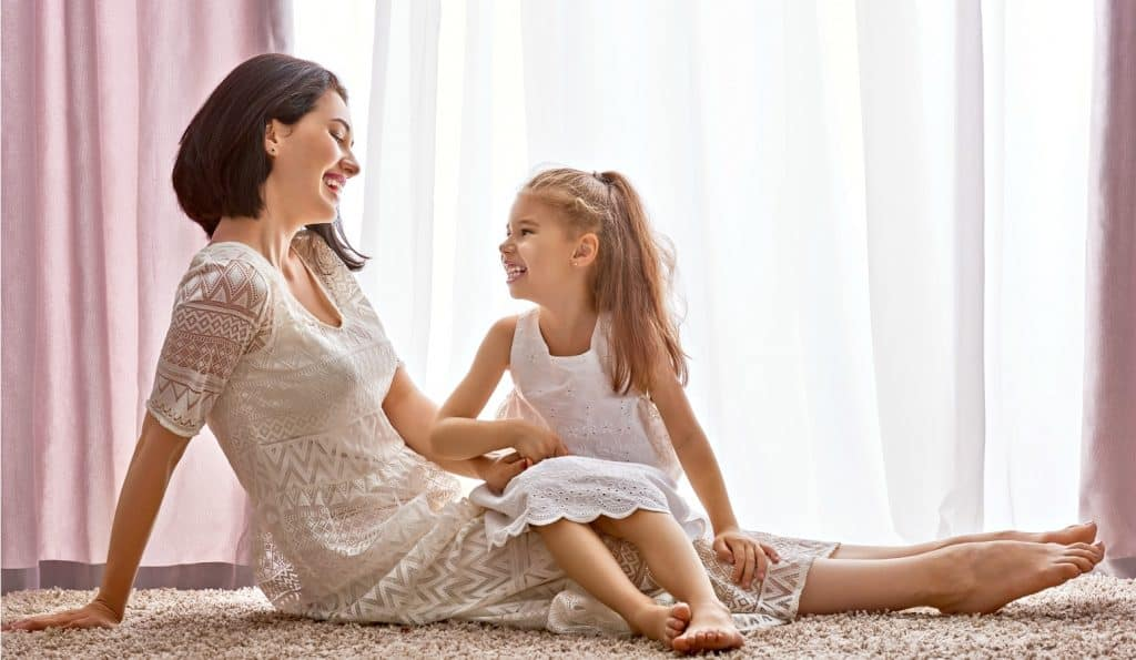 beautiful daughter and mom connecting with kids on living room floor