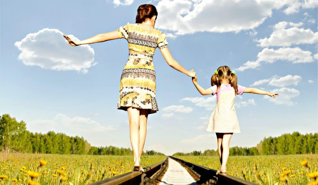 mom walking with daughter on railroad tracks while connecting with kids