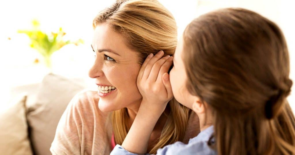 girl whispering to mom while using conversation games for kids to connect with her daughter