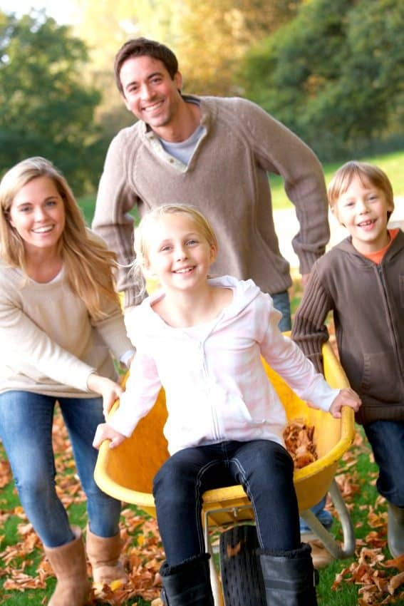 happy family playing in leaves and wheel barrell with fall activities for the family who doesn't celebrate Halloween