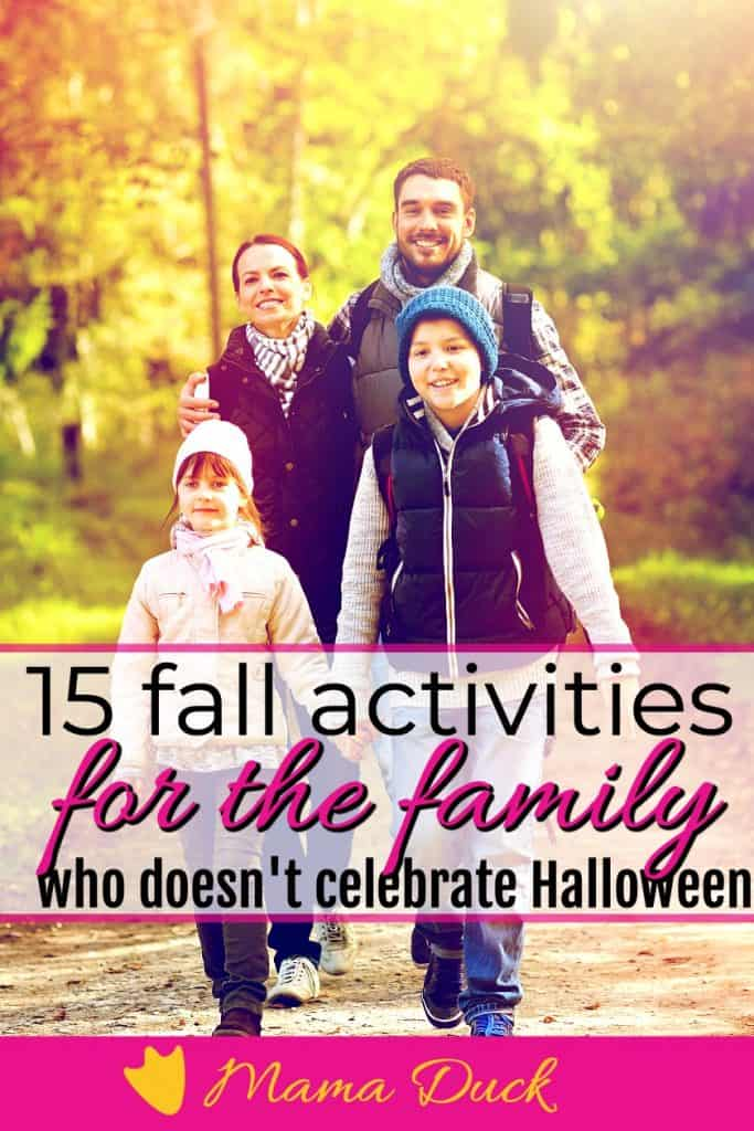 happy family playing in leaves and wheel barrel with fall activities for the family who doesn't celebrate Halloween