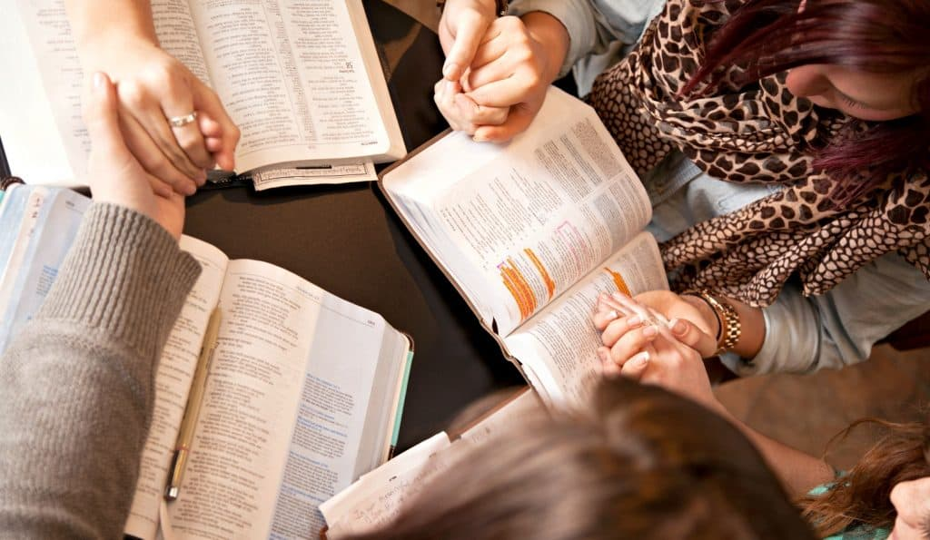 three people holding hands and praying during a family bible study