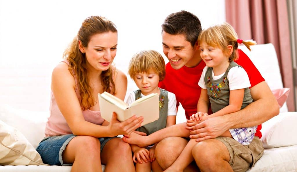 mom dad and two children doing a family bible study
