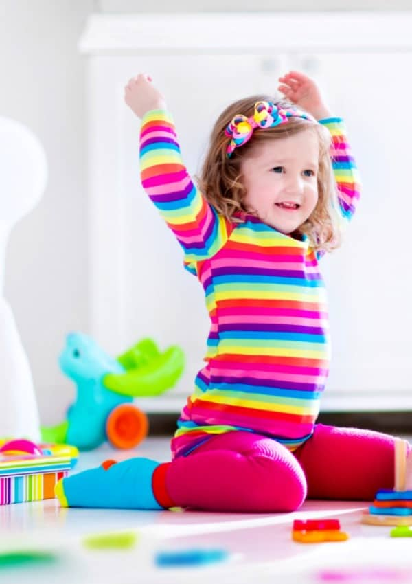 cute little girl in bright colors with arms raised having fun during family game night with toddlers