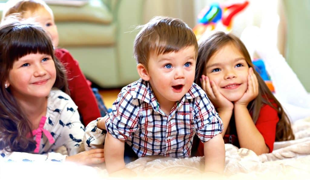 children watching parents excitedly during family game night with toddlers