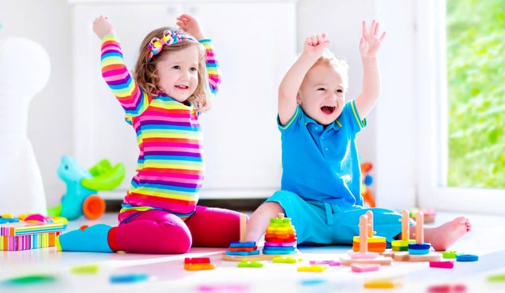 two children playing on the floor during family game night with toddlers