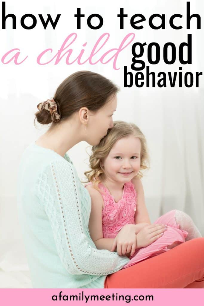 little girl in pink dress displaying trained good behavior as her mom kisses her head while sitting on the floor