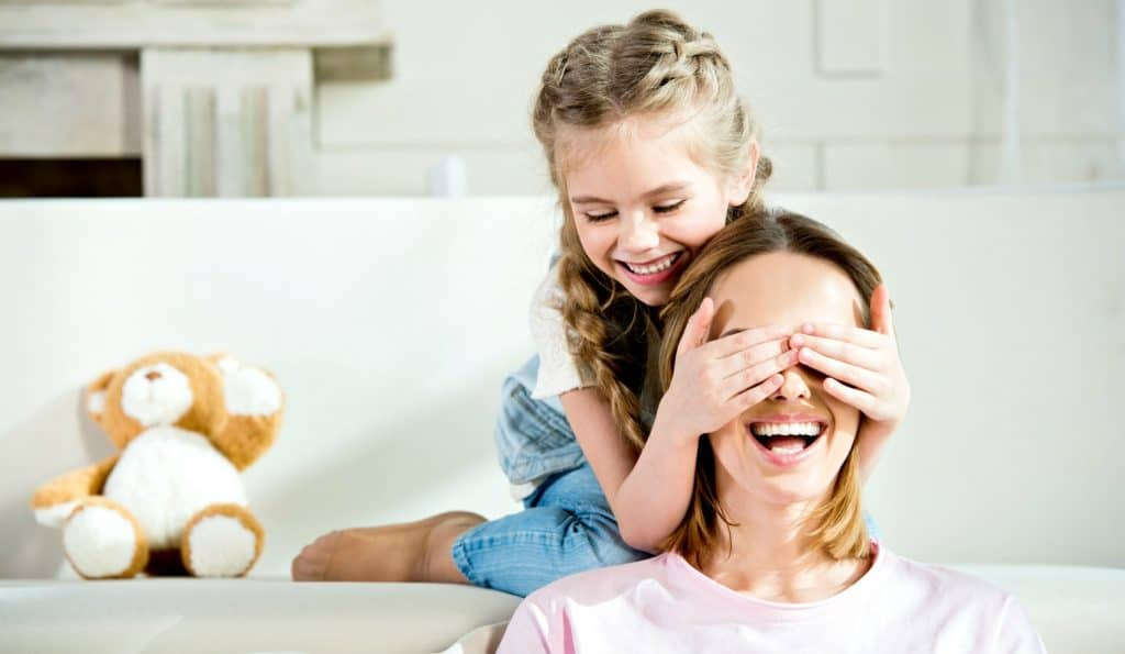 mom and daughter playing peek a boo on the couch during intentional parenting time
