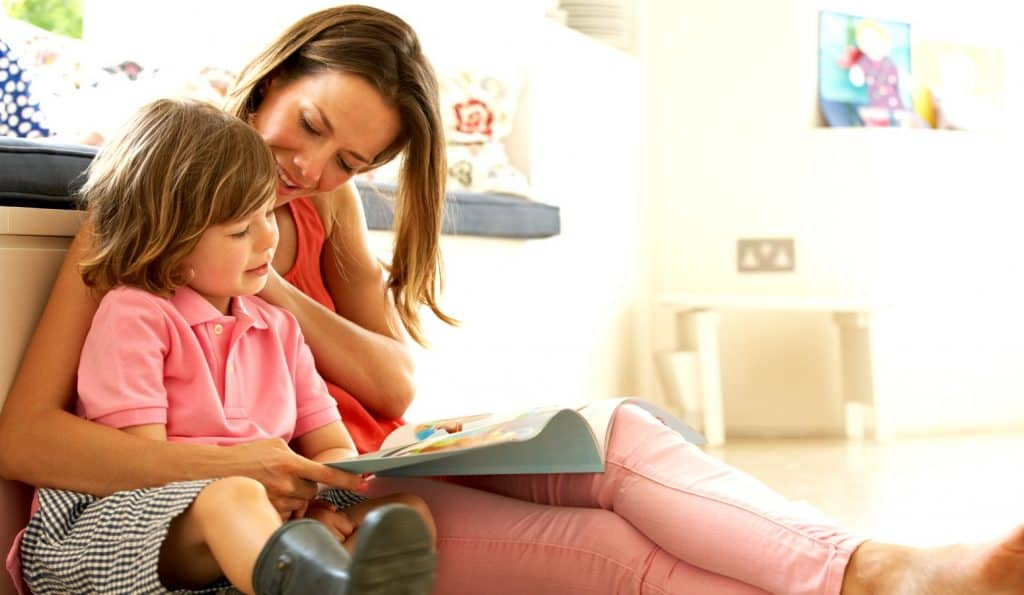 mom and son reading a book on the floor during intentional parenting time