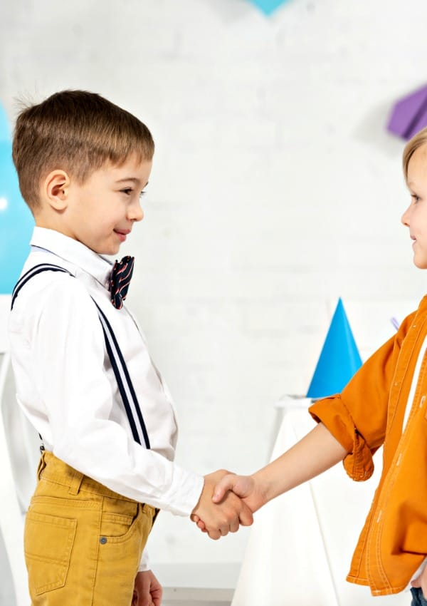 little boys shaking hands showing good life skills for kids