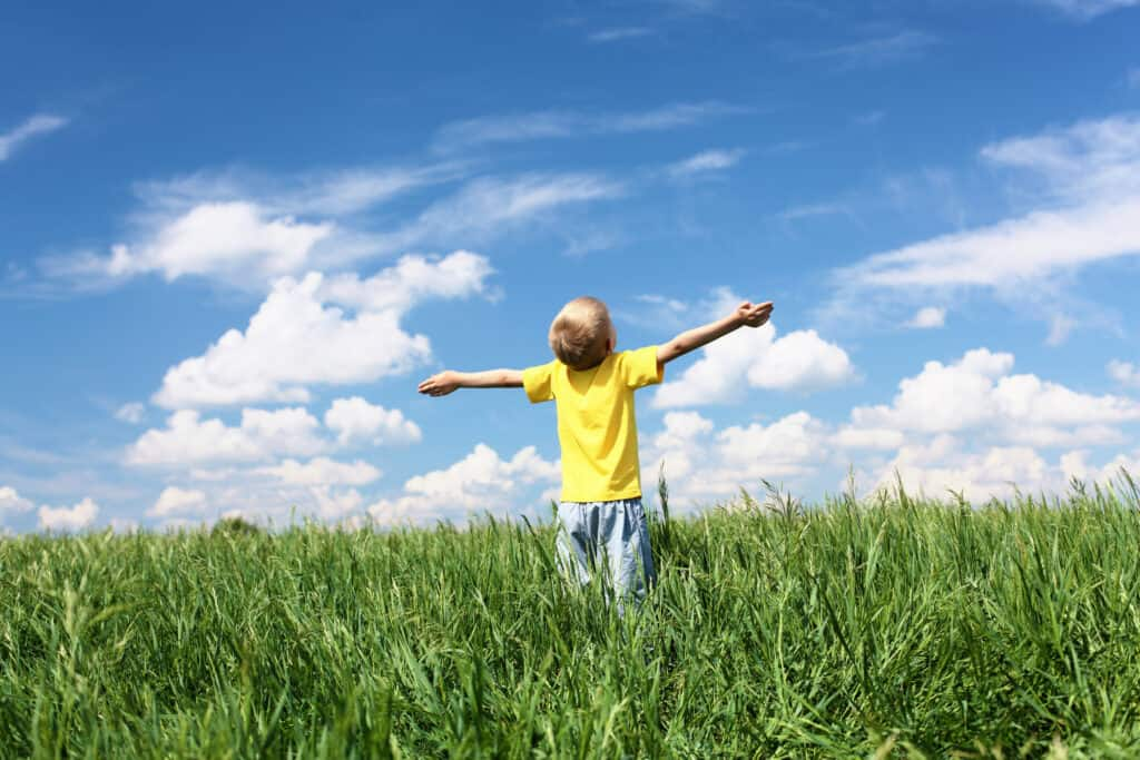 little boy worshipping God in open field and blue sky thanks to biblical parenting principles