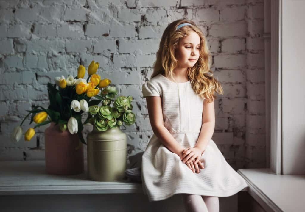 pretty little blonde girl sitting on a table staring out the window