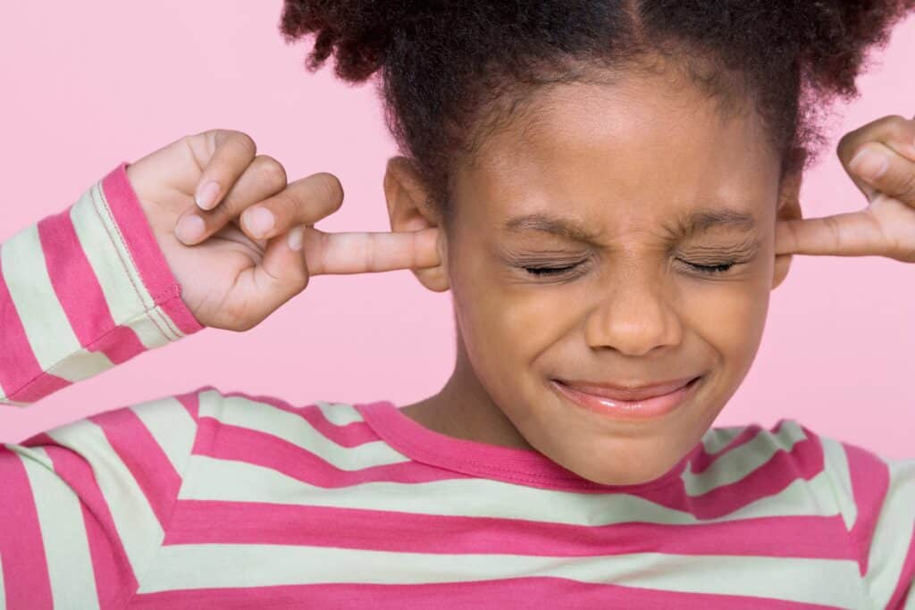 little girl upset with fingers in ears because of strict parents