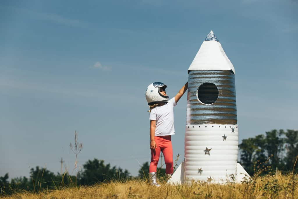 how to help a perfectionist child who has built a homemade rocket and is standing next to it achiever