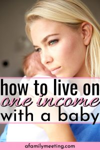 mom holding baby wishing she could be a stay at home mom and know how to live on one income with a baby