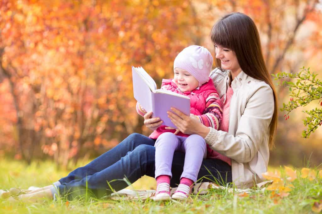 mom and toddler daughter reading together in the fall to reduce family stress