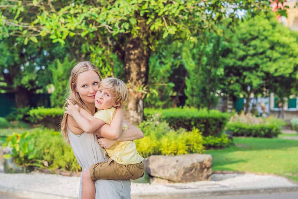 happy blonde mom holding son outside