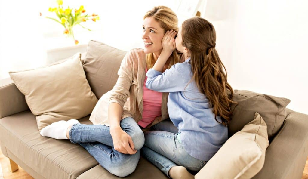 daughter whispering to mom on the couch while mom discovers how parents can influence their children