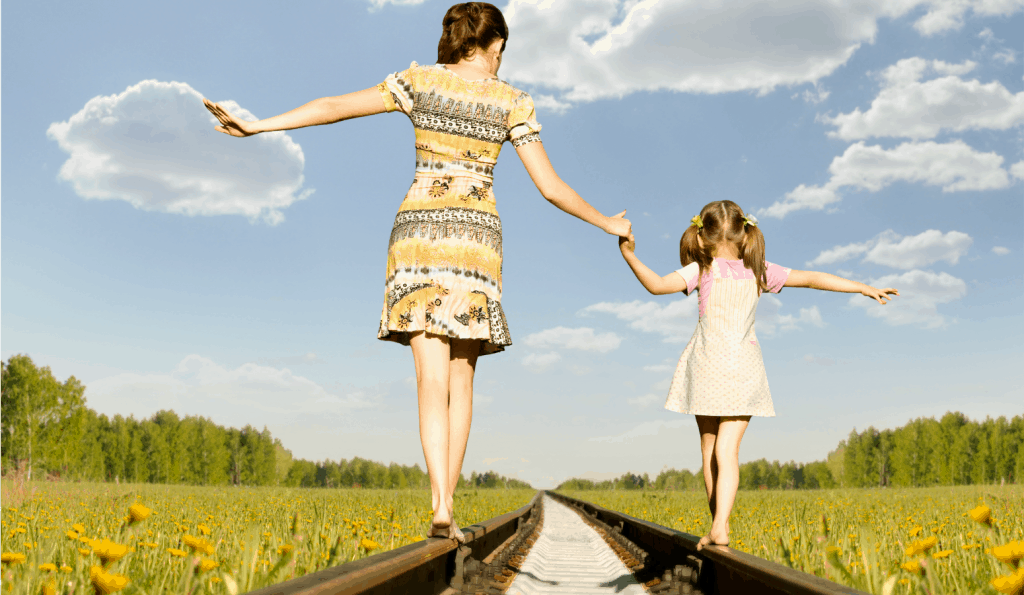 mom and daughter holding hands on railroad tracks while preparing for the teenage years
