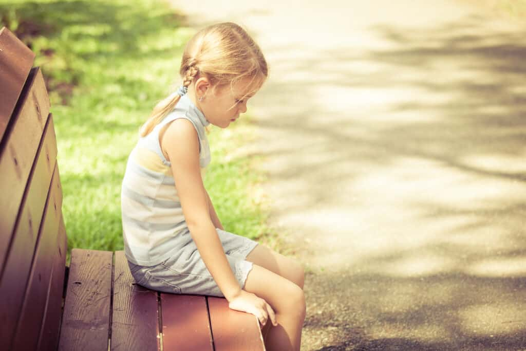 pretty little girl on bench sad because of strict parents