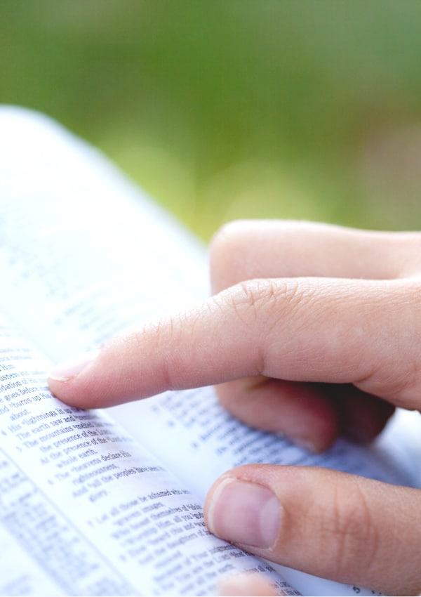womans hand following along as she reads scriptures on parenting