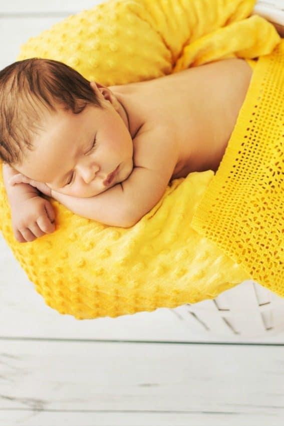 baby sleeping on yellow blanket enjoying the benefits of sleep training