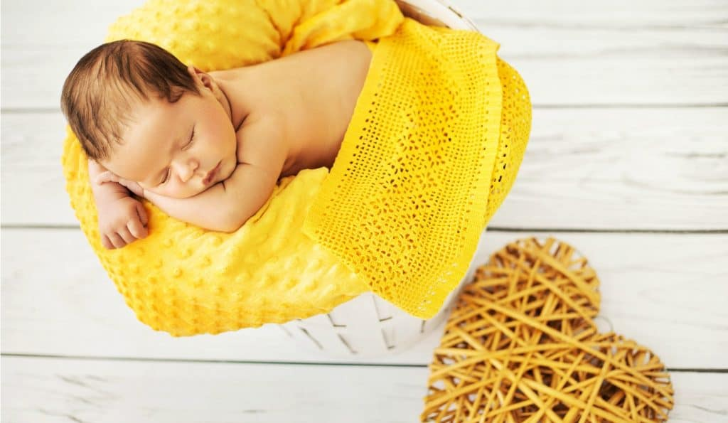 baby sleeping on yellow blanket enjoying the benefits of sleep training