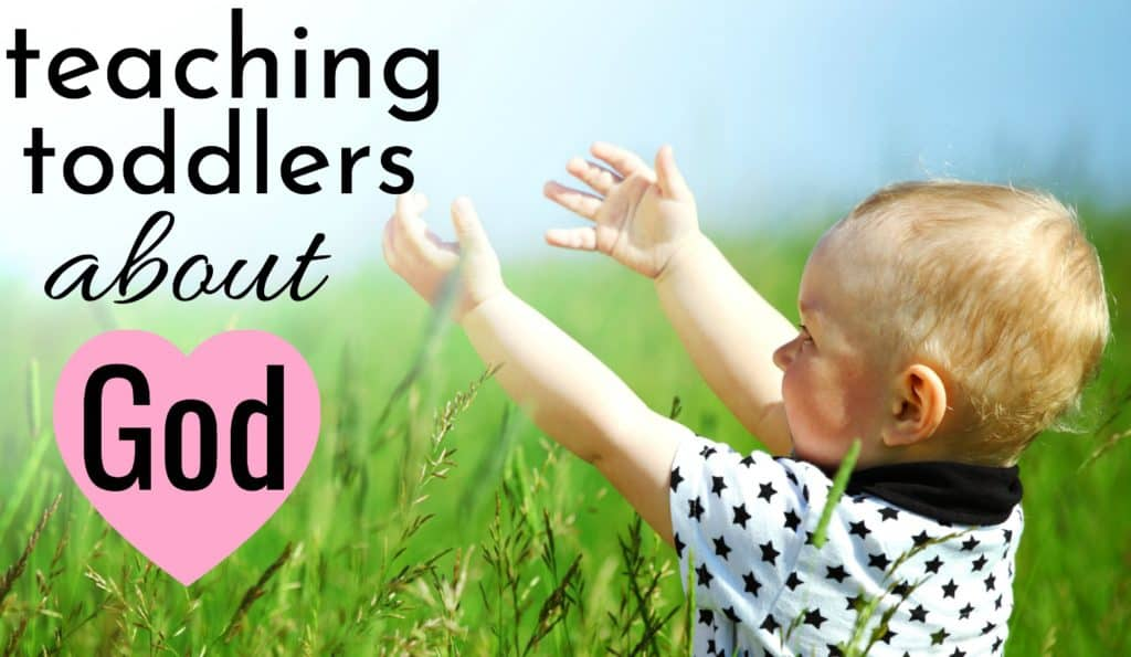 toddler raising his hands to god in a green field