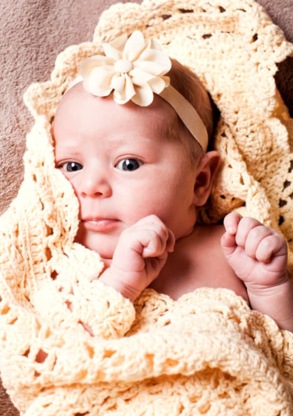 baby girl wrapped in yellow knit blanket when to stop swaddling baby