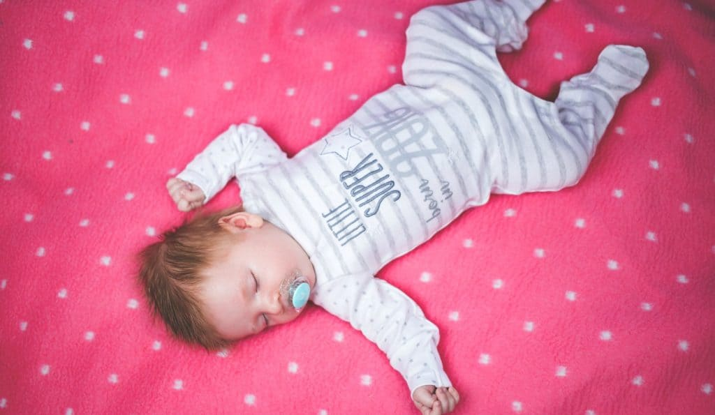 baby girl laying on pink blanket without swaddle enjoying the benefits of sleep training