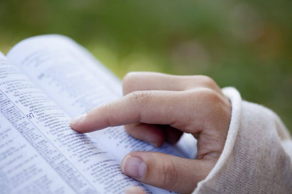 woman's hand reading along with scripture in the bible